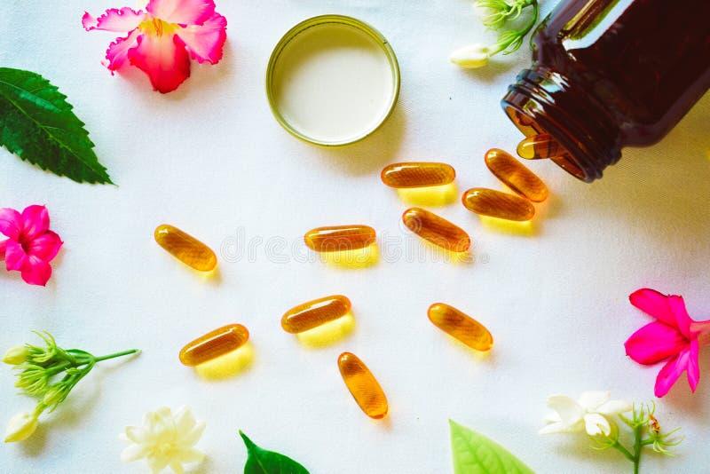 Omega 3 Pillen auf dem Tisch verziert mit farbigen Blumen lizenzfreie stockfotos
