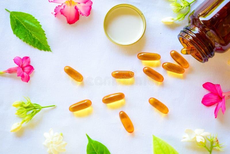 Omega 3 Pillen auf dem Tisch verziert mit farbigen Blumen lizenzfreies stockbild