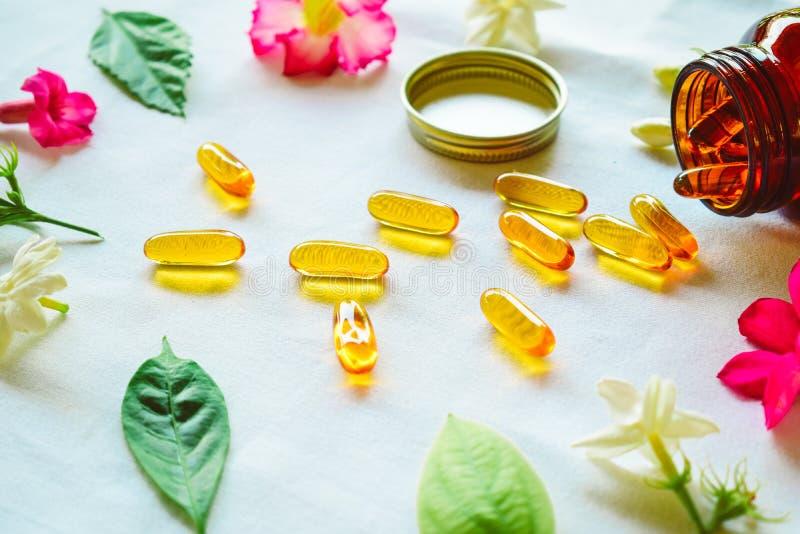 Omega 3 Pillen auf dem Tisch verziert mit farbigen Blumen stockfotografie