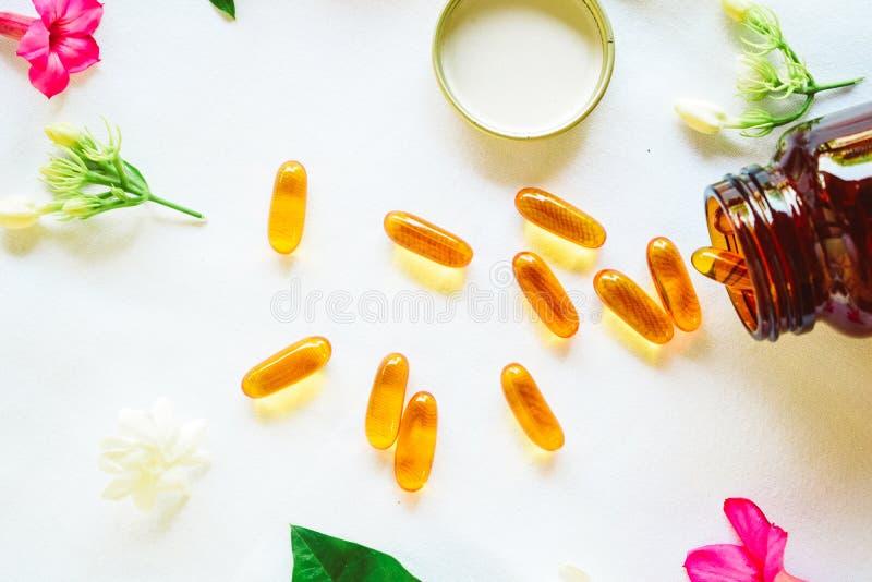 Omega 3 Pillen auf dem Tisch verziert mit farbigen Blumen lizenzfreie stockbilder