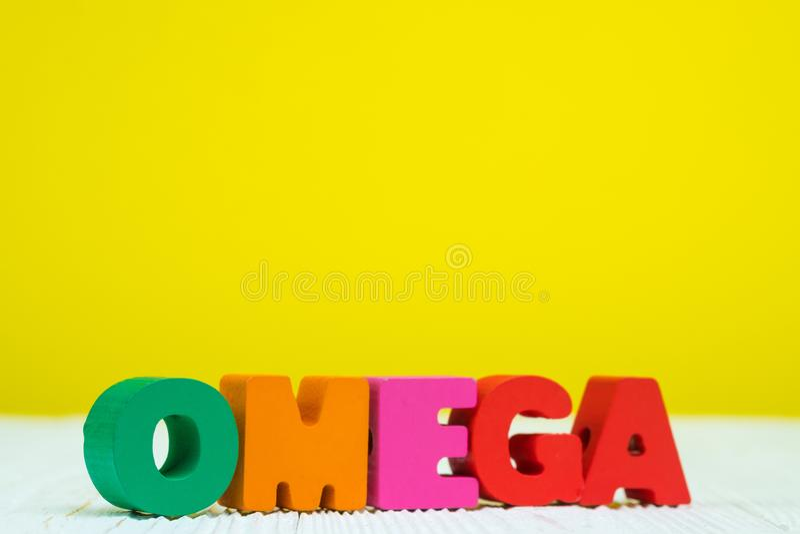 OMEGA teksta abecadło na białym drewnianym stołowym kolor żółty ściany tle fotografia royalty free
