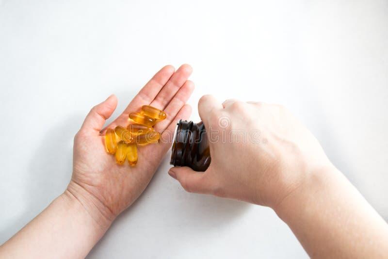 Omega 3 vitaminas en la palma de mujeres da foto de archivo libre de regalías