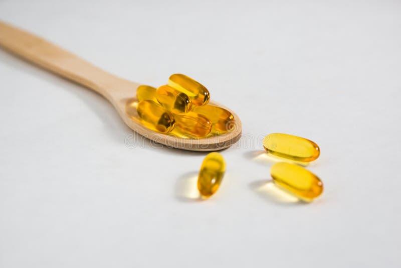 Omega 3 witaminy na drewnianej łyżce na białym tle fotografia royalty free