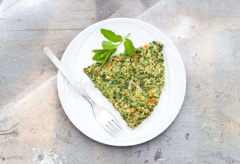 Omelet die van eieren, groene asperge, erwt, wortel, kaas, peterselie en munt, houten achtergrond met natuurlijk licht wordt gema stock foto's