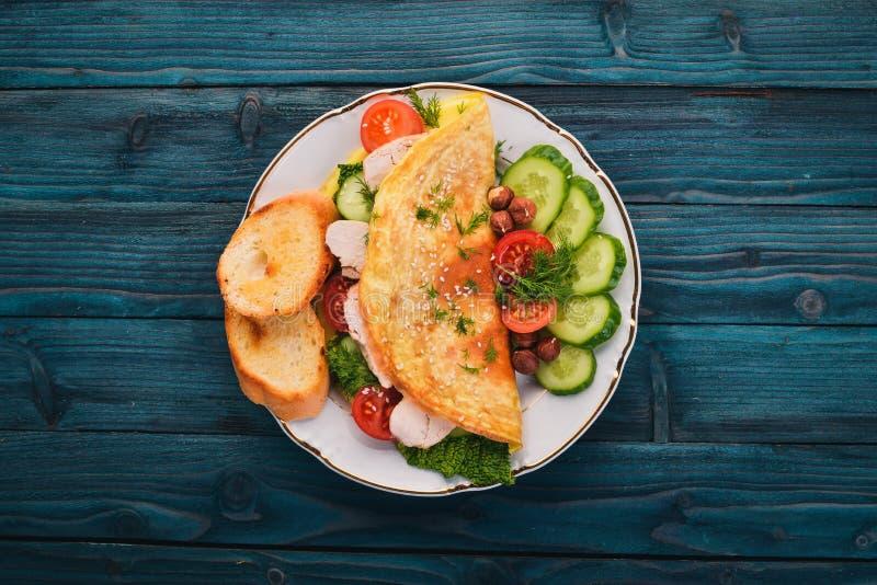 Omelet met kip en verse groenten en noten Op een houten achtergrond stock foto