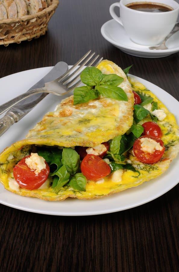 Omelet met spinazie, basilicum, kersentomaten en kaas Adyg stock afbeelding