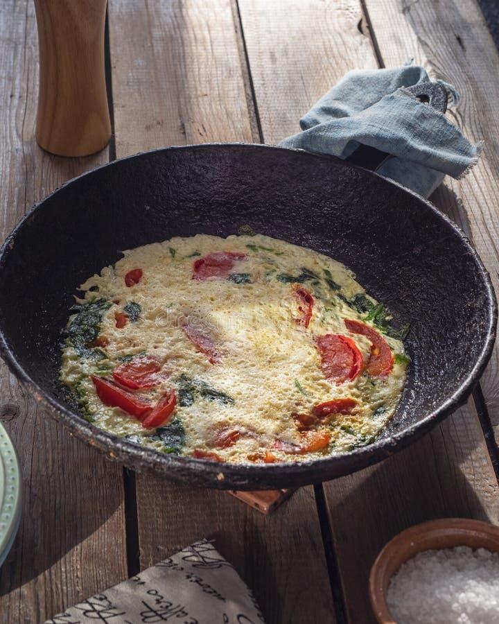 Omelet met tomaten in een ronde gietijzerpan op een oude Raadslijst, een servet met een patroon en een groot zout in een zout royalty-vrije stock afbeeldingen
