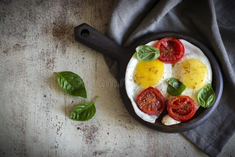 Omelet met tomatenplakken, kruiden en Basilicumbladeren op een pan, die zich op een grijze achtergrond bevindt stock afbeeldingen