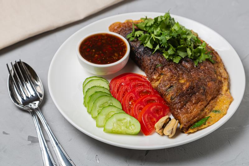 Omelet with mussels. Popular Thai food served with fresh vegetables and sauce on a plate. Omelet with mussels. Popular Thai street food is fast food served with royalty free stock images