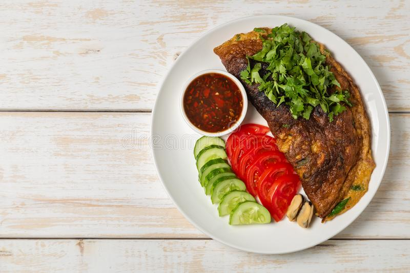 Omelet with mussels. Popular Thai food served with fresh vegetables and sauce on a plate. The view from the top. Copy-space. Omelet with mussels. Popular Thai royalty free stock photography