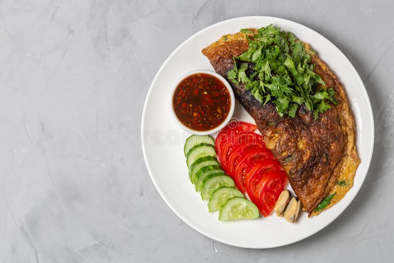 Omelet with mussels. Popular Thai food served with fresh vegetables and sauce on a plate. The view from the top. Copy-space. Omelet with mussels. Popular Thai stock photo
