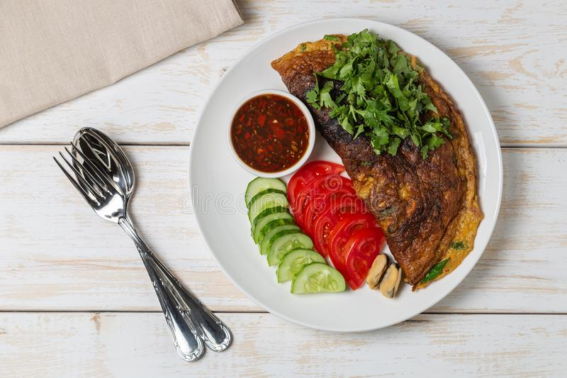 Omelet with mussels. Popular Thai food served with fresh vegetables and sauce on a plate. The view from the top. Copy-space. Omelet with mussels. Popular Thai stock image