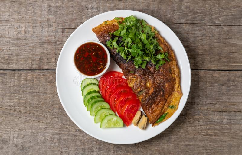 Omelet with mussels. Popular Thai food served with fresh vegetables and sauce on a plate. The view from the top. Copy-space. Omelet with mussels. Popular Thai royalty free stock image