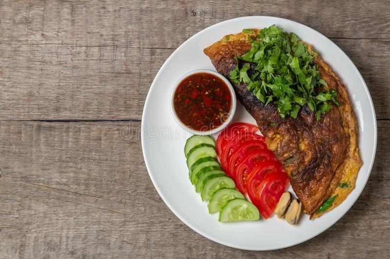 Omelet with mussels. Popular Thai food served with fresh vegetables and sauce on a plate. The view from the top. Copy-space. Omelet with mussels. Popular Thai royalty free stock images