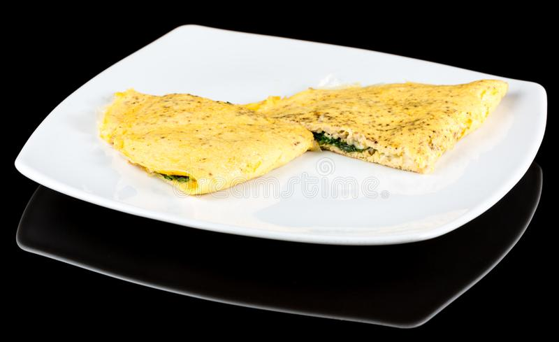 Omelet with organic spinach, cheese and mushrooms isolated on bl royalty free stock image