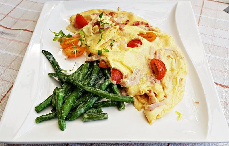 Omelet with sausage and sliced cherry tomatoes and fried green beans on a white plate royalty free stock photos