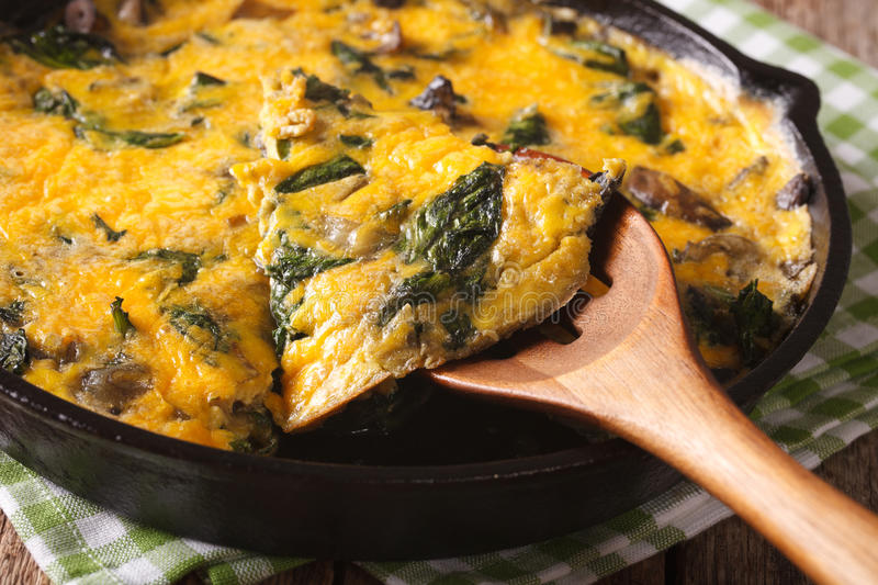 Omelet with spinach, cheese and mushrooms in a pan close-up. hor royalty free stock images