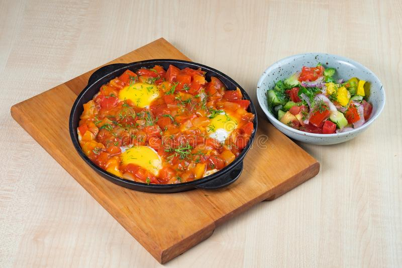 Omelet with sweet peppers in a griddle on a wooden board and vegetable salad stock photo
