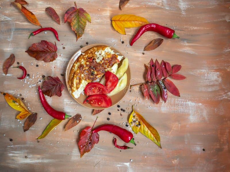 Omelet van courgettes en eierennutstomaat, ceramische schotel houten achtergrond stock foto's