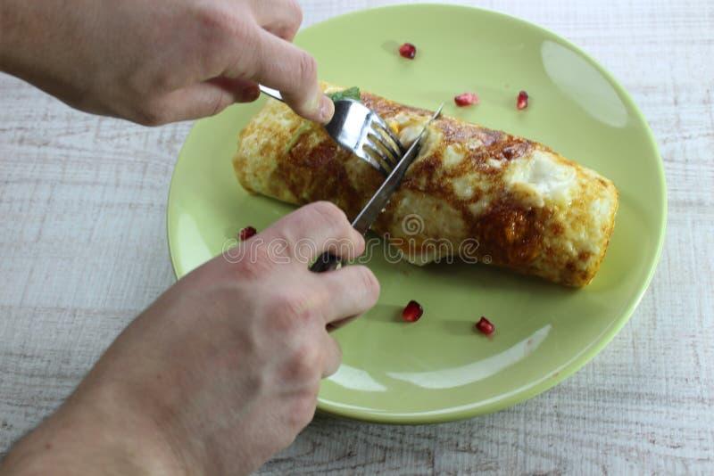 Omelet van het ochtend de ontbijt gebraden die ei met courgette op de groene plaat wordt gevuld Het snijden van het met een mes e stock afbeelding