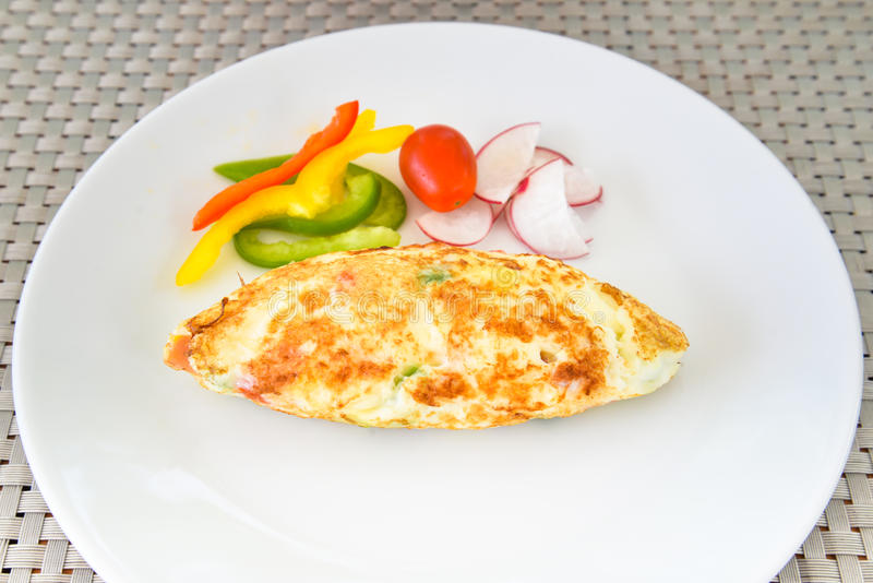 Omelet with vegetables on white plate royalty free stock photography