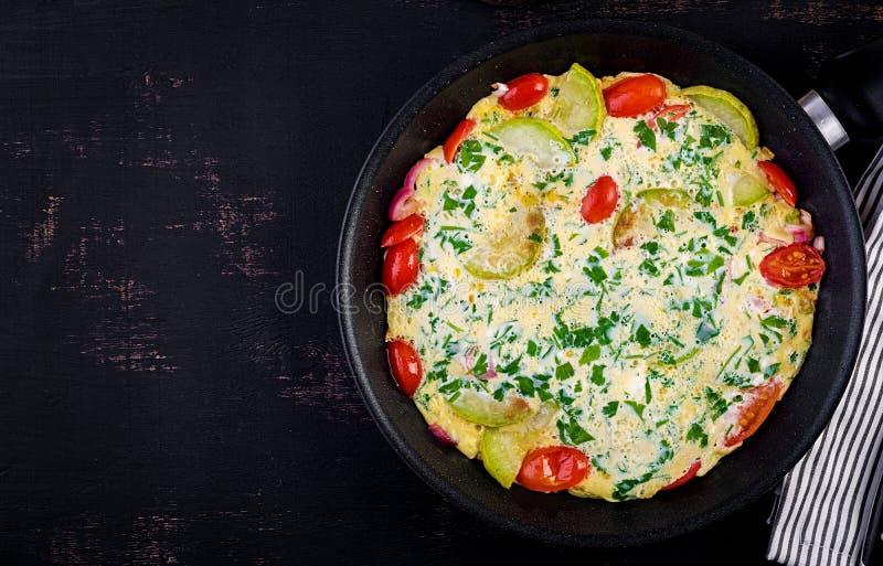 Omelet z pomidorami, cukinią i cebulą czerwoną na ciemnym stole obraz stock