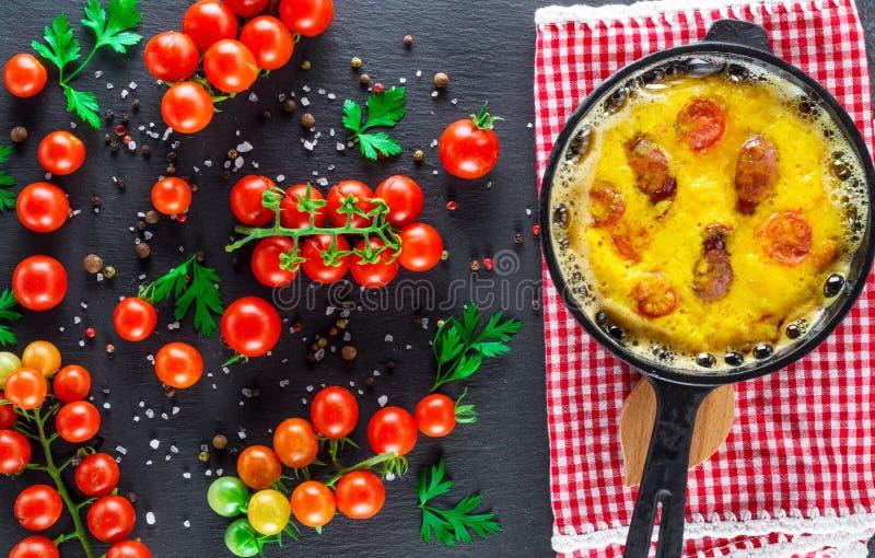 A omeleta com salsichas e galinha eggs em um potenciômetro redondo do ferro fundido fotos de stock royalty free