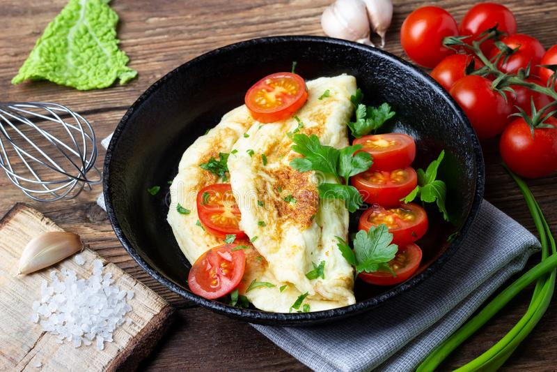 Omeleta com tomates de cereja e salsa verde fresca em uma bandeja preta do ferro fotos de stock royalty free