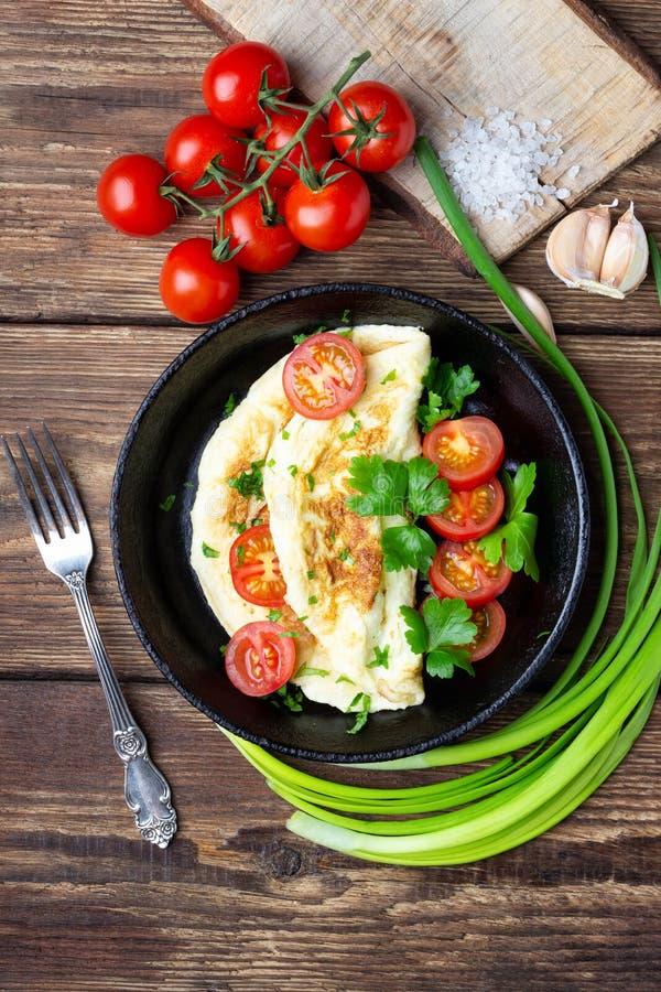 Omeleta com tomates de cereja e salsa verde fresca em uma bandeja preta do ferro imagem de stock royalty free