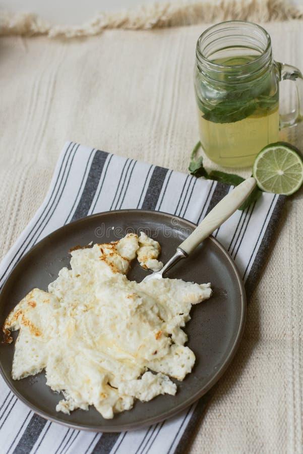 Omeleta cozinhada deliciosa em um guardanapo cinzento e em um tapete bege Limonada caseiro e ovos mexidos para pratos escuros do  fotos de stock