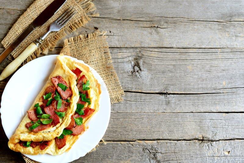 Omeleta enchida fritada Omeleta saboroso com bacon fritado e salsa fresca em uma placa, forquilha, faca no fundo de madeira velho fotografia de stock royalty free