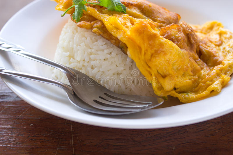Omeleta no arroz, no alimento, no arroz, no amarelo, na forquilha e na colher fotografia de stock royalty free