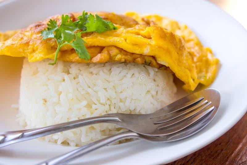 Omeleta no arroz, no alimento, no arroz, no amarelo, na forquilha e na colher foto de stock