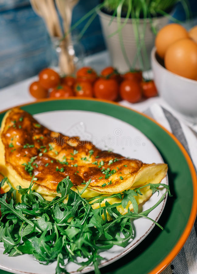 Omelete and ruccola leaves. Omelete, cherry tomatoes and ruccola leaves stock photos