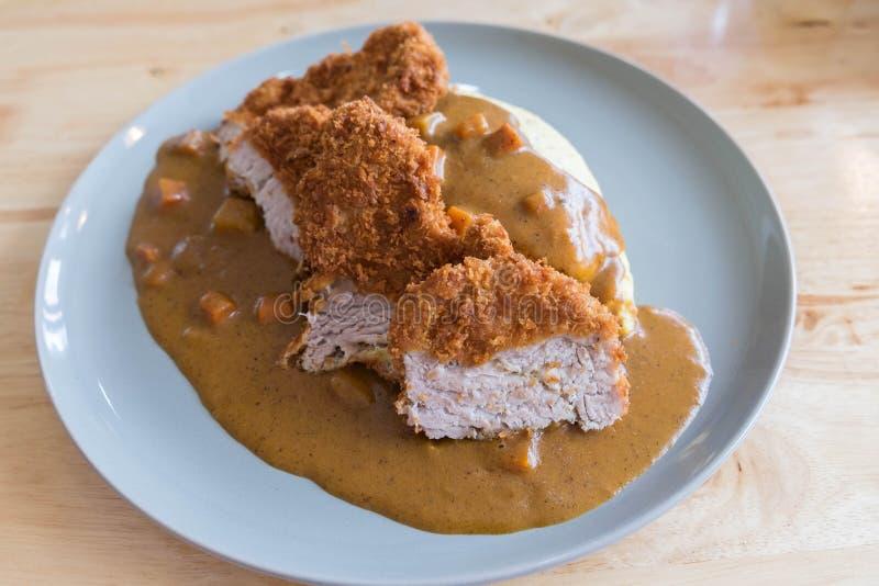Omeletrijst met Japanse Kerrie en Gepaneerd Diep Fried Pork Cutlet op Moderne Houten Lijst royalty-vrije stock afbeeldingen