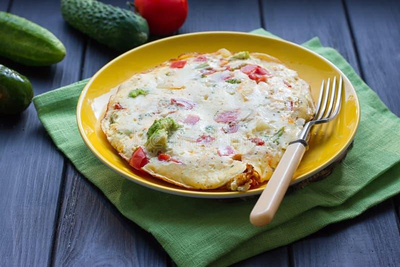 Omelett från fega ägg med ost, nya grönsaker - gurka och tomaten royaltyfri foto