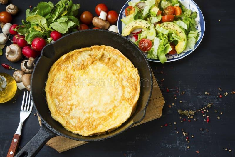 Omelett i en panna med grönsaker sallad, champinjoner, rädisa och s arkivfoto