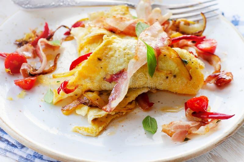 Omelett med bacon och grönsaker för en sund frukost royaltyfri fotografi