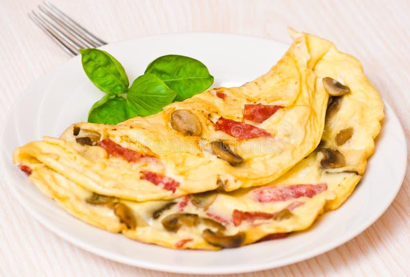 Omelett med champinjoner och salami arkivbild