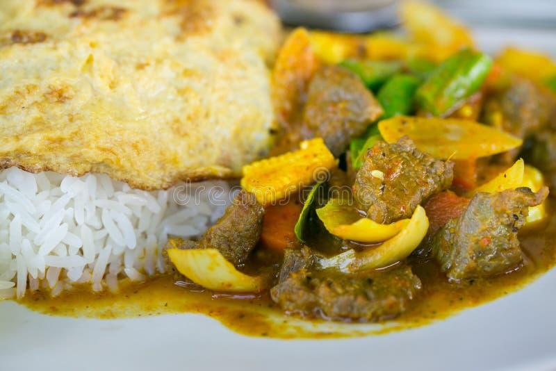 Omelett med ris och kryddigt currynötkött arkivfoto