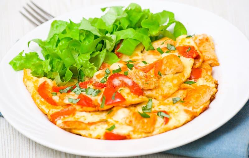 Omelett mit Scheiben der Hühnerbrust und des Gemüses stockbild