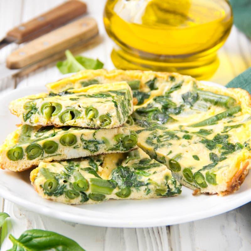 Omelett mit Spinat und gr?nen Bohnen, gesunde Nahrung Ei und Milch Frittata, köstliches Frühstück auf weißem hölzernem Hintergrun lizenzfreies stockfoto