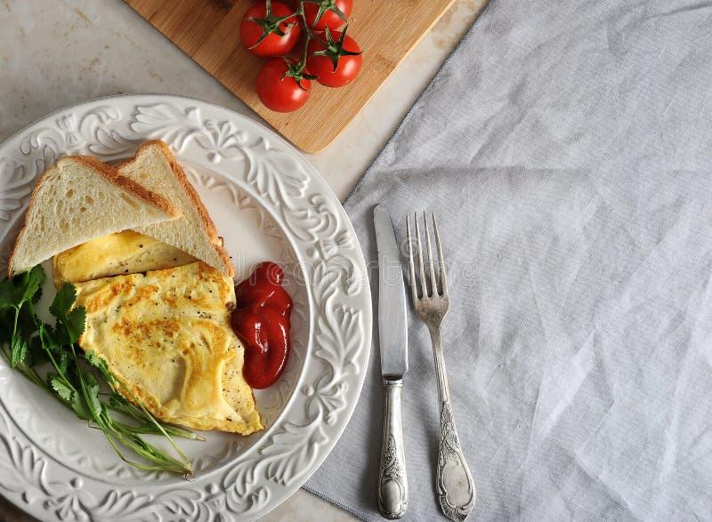 Omelett på en platta, persilja, tomater, rostat bröd, ketchup fotografering för bildbyråer