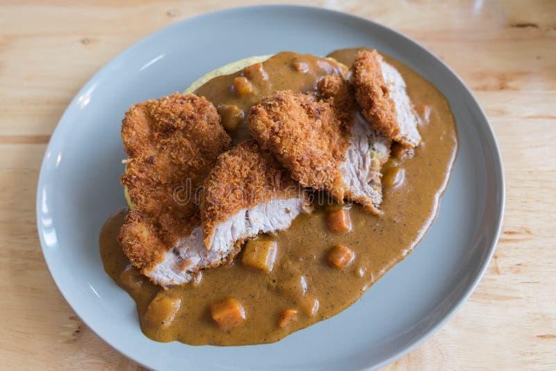 Omelett-Reis mit japanischem Curry und paniertem tiefem Fried Pork Cutlet auf moderner hölzerner Tabelle stockfotografie