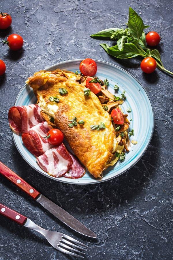 Omelette avec des tomates, des champignons et le lard Petit déjeuner sur le fond en pierre photographie stock