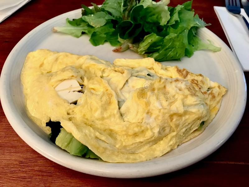 Omelette bianca con gli spinaci del bambino ed il formaggio di capra serviti con l'insalata di verdi fotografie stock