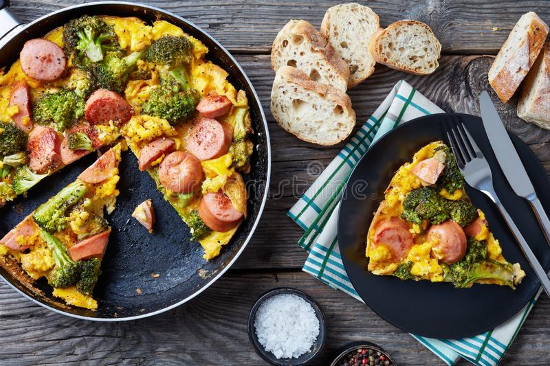 Omelette with broccoli and sausages in a skillet royalty free stock photography