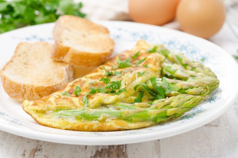 Omelette con asparago, verdi e pane tostato, fuoco selettivo fotografia stock