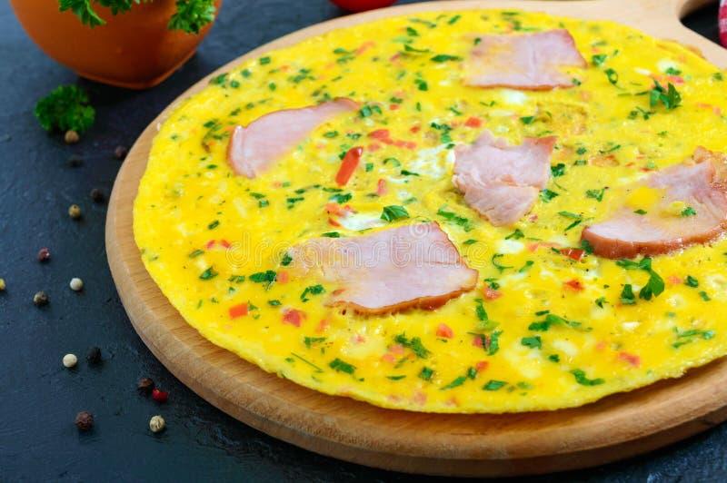 Omelette con il prosciutto, formaggio, verdi su un bordo di legno su un fondo nero Fritata - una prima colazione deliziosa e sana immagine stock libera da diritti