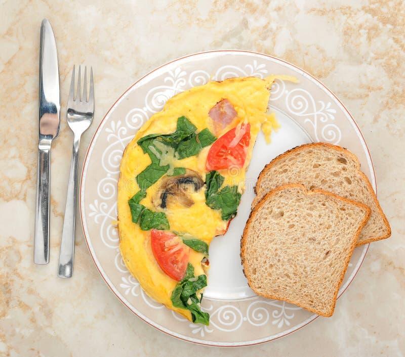 Omelette con spinaci, i pomodori ed i funghi sul piatto rotondo fotografie stock libere da diritti